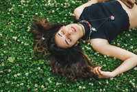 High angle view of woman with nose ring lying on clover covered grass, eyes closed 11015273832| 写真素材・ストックフォト・画像・イラスト素材|アマナイメージズ