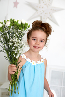 Girl with carnations against white wall with stars 11015274366| 写真素材・ストックフォト・画像・イラスト素材|アマナイメージズ