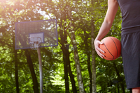 Cropped detail of young male basketball player holding ball in front of basketball hoop