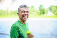 Portrait of senior man weight training with dumbbells by river