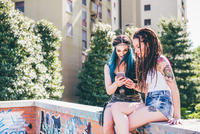 Two young women on wall reading smartphone texts in urban housing estate 11015288355| 写真素材・ストックフォト・画像・イラスト素材|アマナイメージズ