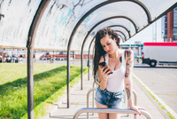 Young woman with dreadlocks reading smartphone in urban bus shelter 11015288375| 写真素材・ストックフォト・画像・イラスト素材|アマナイメージズ