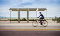 Blurred motion of cyclist cycling along coastal road, Cagliari, Italy