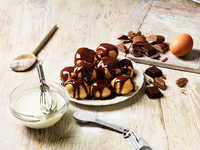 Profiteroles with hot chocolate sauce, cream filling in bowl with whisk, wooden spoon with flour, egg, sugar in measuring spoon, 11015288690| 写真素材・ストックフォト・画像・イラスト素材|アマナイメージズ