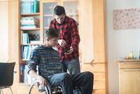 Young man using wheelchair reading smartphone texts with friend in kitchen 11015288845| 写真素材・ストックフォト・画像・イラスト素材|アマナイメージズ