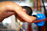 Boxer leaning on ropes of boxing ring
