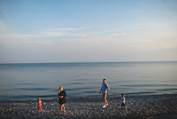 Mid adult parents strolling with boy and girl on pebble beach at Lake Ontario, Oshawa, Canada