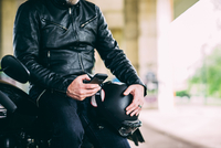 Mid section of mature male motorcyclist sitting on motorcycle texting on smartphone 11015290283| 写真素材・ストックフォト・画像・イラスト素材|アマナイメージズ