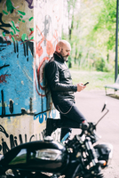 Mature male motorcyclist leaning against wall reading smartphone texts 11015290285| 写真素材・ストックフォト・画像・イラスト素材|アマナイメージズ