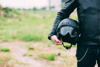 Mid section of male motorcyclist standing on wasteland holding helmet 11015290321| 写真素材・ストックフォト・画像・イラスト素材|アマナイメージズ