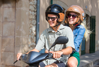 Young couple riding moped together through village, Majorca, Spain 11015290372| 写真素材・ストックフォト・画像・イラスト素材|アマナイメージズ