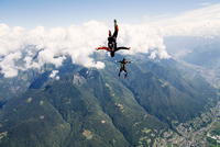 Freestyle skydiving team training together. One man  performing air-ballet, another jumper is filming with video camera on helme