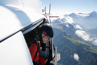 Female sky diver in helicopter checking for exit over mountain, Interlaken, Berne, Switzerland 11015291070| 写真素材・ストックフォト・画像・イラスト素材|アマナイメージズ