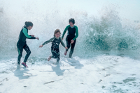 Family wearing wet suits running from waves 11015294600| 写真素材・ストックフォト・画像・イラスト素材|アマナイメージズ