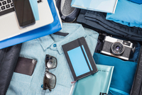 Overhead detail of packed suitcase with blue shirt,  retro camera, laptop, smartphone and notebook 11015295430| 写真素材・ストックフォト・画像・イラスト素材|アマナイメージズ