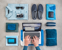 Overhead view of man's hands typing on laptop surrounded by travel packing items, with blue shirt,  retro camera, wash bag and n 11015295432| 写真素材・ストックフォト・画像・イラスト素材|アマナイメージズ