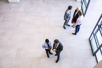 High angle view of businesswoman and businessmen having discussions in office atrium 11015295608| 写真素材・ストックフォト・画像・イラスト素材|アマナイメージズ