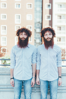 Portrait of identical male hipster twins standing on apartment roof terrace 11015295820| 写真素材・ストックフォト・画像・イラスト素材|アマナイメージズ