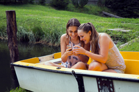 Two young female friends reading smartphone texts in rowing boat on lakeside 11015295878| 写真素材・ストックフォト・画像・イラスト素材|アマナイメージズ
