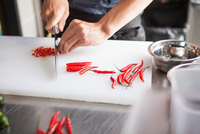 Cropped view of man slicing red chilli peppers 11015296031| 写真素材・ストックフォト・画像・イラスト素材|アマナイメージズ