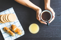 Overhead view of woman's hands holding coffee cup 11015296606| 写真素材・ストックフォト・画像・イラスト素材|アマナイメージズ