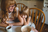 Mother and daughter cuddling at breakfast table 11015296628| 写真素材・ストックフォト・画像・イラスト素材|アマナイメージズ