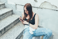 Young woman sitting on stairway reading smartphone texts 11015297819| 写真素材・ストックフォト・画像・イラスト素材|アマナイメージズ