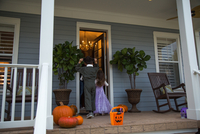Brother and sister trick or treating at neighbour's front door 11015300531| 写真素材・ストックフォト・画像・イラスト素材|アマナイメージズ