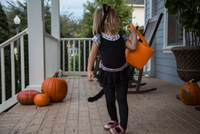 Girl trick or treating in cat costume looking over her shoulder on porch 11015300537| 写真素材・ストックフォト・画像・イラスト素材|アマナイメージズ