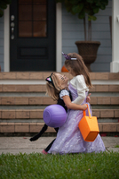 Two sisters trick or treating in cat and fairy costumes hugging at porch stairway 11015300544| 写真素材・ストックフォト・画像・イラスト素材|アマナイメージズ