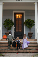 Rear view of boy and sisters trick or treating moving up porch stairway 11015300545| 写真素材・ストックフォト・画像・イラスト素材|アマナイメージズ