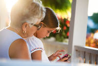 Girl playing smartphone game sitting on grandmother's lap in porch at sunset 11015301724| 写真素材・ストックフォト・画像・イラスト素材|アマナイメージズ