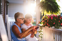 Girl and grandmother playing smartphone game on porch at sunset 11015301725| 写真素材・ストックフォト・画像・イラスト素材|アマナイメージズ