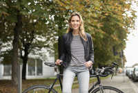 Portrait of mid adult woman leaning against bicycle in city park 11015303897| 写真素材・ストックフォト・画像・イラスト素材|アマナイメージズ