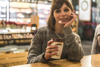 Portrait of young woman sitting in coffee shop, holding coffee cup 11015304689| 写真素材・ストックフォト・画像・イラスト素材|アマナイメージズ