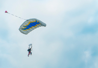 View of tandem parachuting down against cloudy sky 11015304863| 写真素材・ストックフォト・画像・イラスト素材|アマナイメージズ