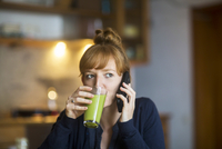 Young woman drink smoothie, using smartphone 11015307411| 写真素材・ストックフォト・画像・イラスト素材|アマナイメージズ