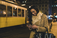 Young woman in city at night, using smartphone, Lisbon, Portugal 11015307662| 写真素材・ストックフォト・画像・イラスト素材|アマナイメージズ