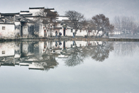 Mirror image of bare trees and traditional houses by lake, Hongcun Village, Anhui Province, China 11015307802| 写真素材・ストックフォト・画像・イラスト素材|アマナイメージズ