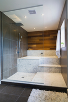 Wet room style glass shower stall with grey and white marble steps and red cedar wooden wall, Quebec, Canada