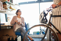 Woman in office with coffee chatting to colleague 11015313634| 写真素材・ストックフォト・画像・イラスト素材|アマナイメージズ
