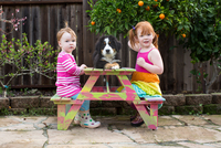 Two young sisters sitting on garden bench with pet dog 11015317088| 写真素材・ストックフォト・画像・イラスト素材|アマナイメージズ
