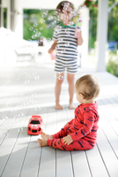 Male toddler sitting on porch watching boy blowing bubbles 11015317112| 写真素材・ストックフォト・画像・イラスト素材|アマナイメージズ