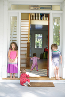 Boy and girl watching toddler crawling in house doorway 11015317115| 写真素材・ストックフォト・画像・イラスト素材|アマナイメージズ