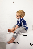 Male toddler sitting gazing from toy chest