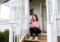 Young woman sitting on porch stairs with coffee cup looking at smartphone 11015319815| 写真素材・ストックフォト・画像・イラスト素材|アマナイメージズ