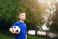 Boy holding soccer ball looking away
