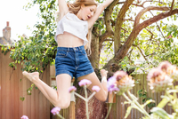 Teenage girl in garden jumping in air