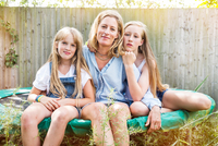 Portrait of mother and daughters sitting on trampoline looking at camera smiling