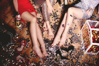Three woman sitting on floor at party, shoes off, surrounded by glitter, low section